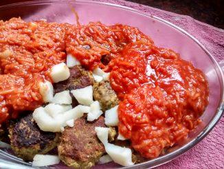albóndigas lentejas con salsa, bañadas con salsa y cubos de papa