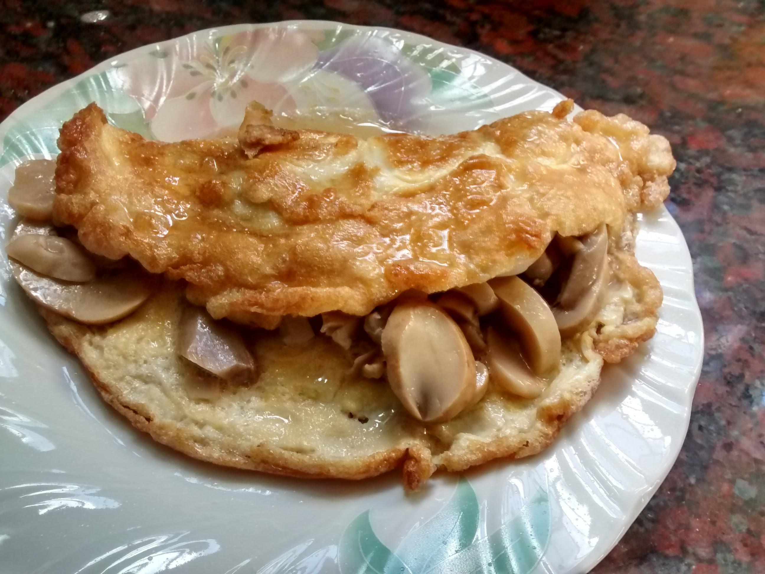 omelette de champiñones individual, color amarillo por el huevo combinado con el color de los champiñones, presentado con el relleno casi a la vista